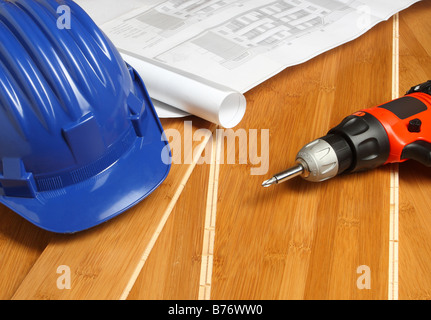 blue helmet red drill and bluprint on wood floor - Stock Photo