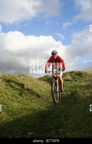Young female mountain biker descending into Long Dale in the Derbyshire Dales of the Peak District - Stock Photo