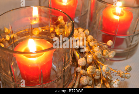 Lighted red candles in glass containers - Stock Photo
