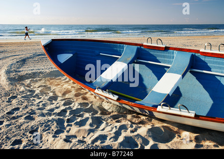 Woman in background walking on beach and small boat, New Jersey, USA - Stock Photo