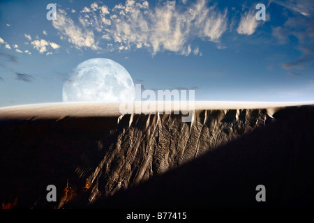 A larger than life depiction of the full moon rising above a sand dune at White Sands National Monument, New Mexico. - Stock Photo