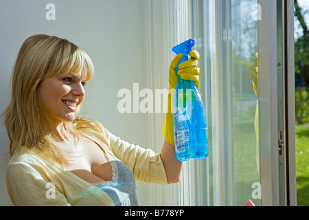 young woman, housewife cleaning windows - Stock Photo