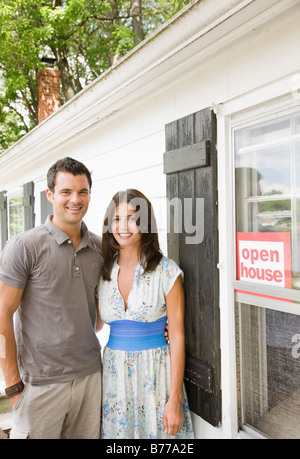 "Young couple posing front of house ""Open House"" sign - Stock Photo"