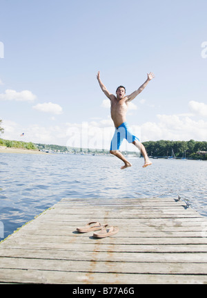 Portrait of man jumping off dock into lake - Stock Photo