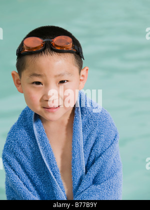 Boy wrapped towel posing front of swimming pool - Stock Photo