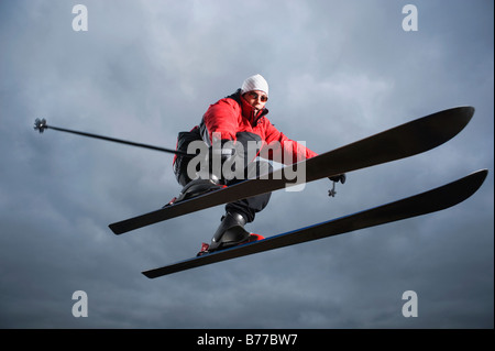 Portrait of downhill skier mid-air - Stock Photo