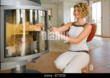 Frau macht Feuer in einem Ofen, Woman makes fires in a furnace - Stock Photo