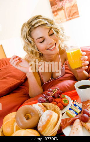 Junge Frau fruehstueckt im Bett, Young woman has breakfast in bed - Stock Photo