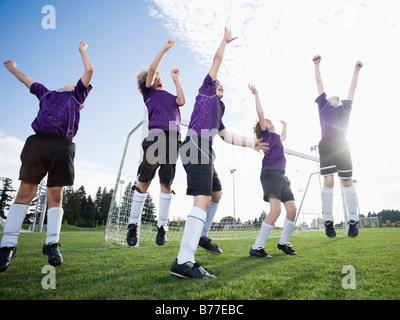 Boys soccer team celebrating on field - Stock Photo