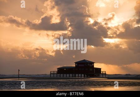 Restaurant Strandbar at sunset, built on stilts off the St. Peter-Ording beach, Eiderstedt Peninsula, Schleswig - Stock Photo