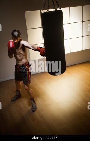 Boxer training punching bag - Stock Photo