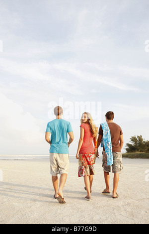 Friends walking on beach - Stock Photo