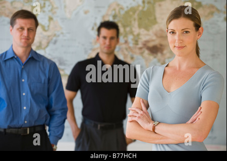 Portrait of business people standing front of map - Stock Photo
