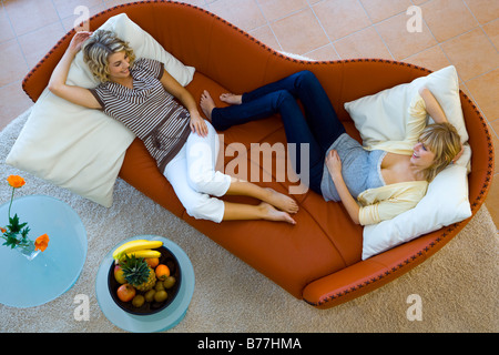two women, friends relaxing on a leather sofa at home - Stock Photo