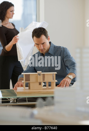 Architects working blueprints and building model - Stock Photo