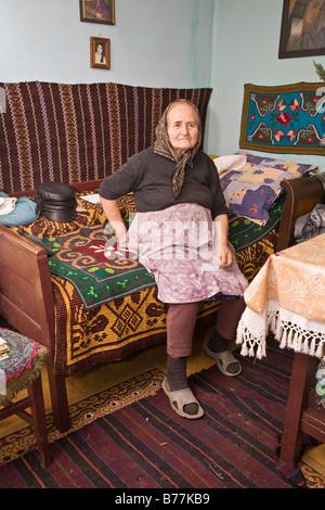 Romanian woman wearing a headscarf, sitting in her living room in Bezded, Salaj, Transylvania, Romania, Europe - Stock Photo