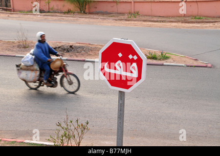 Man on a moped, stop sign in Arabic, Marrakech, Morocco, Africa - Stock Photo