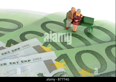 Figures of two seniors sitting on Euro banknotes, symbolic image for pension plan, retirement - Stock Photo