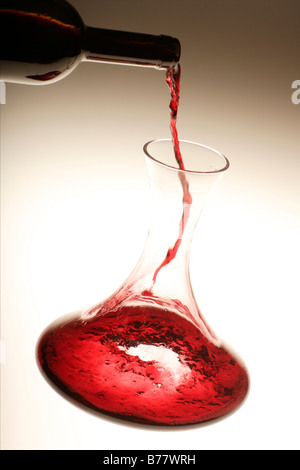 Red wine being poured into a decanter - Stock Photo