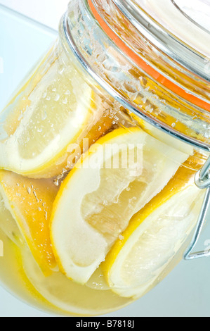 Parfait jar of preserved lemons. Quarters of lemons are covered in salt then topped up with lemon juice. Used in - Stock Photo