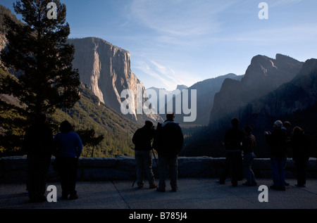 Tourists enjoy the view of YOSEMITE VALLEY showing EL CAPITAN and HALF DOME YOSEMITE NATIONAL PARK CALIFORNIA - Stock Photo