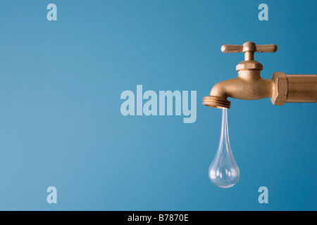 giant drop of water drips from faucet - Stock Photo