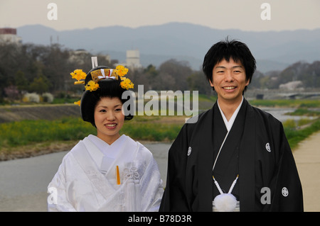 Traditional Japanese wedding couple wearing kimonos, bride with wedding hairstyle, on the Kamigamo River, Kyoto, - Stock Photo