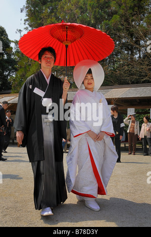 Japanese wedding couple wearing traditional wedding kimonos, bride wearing a bonnet, groom holding a red parasol in front of th