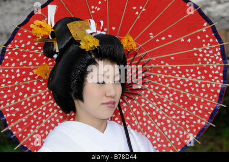 Bride wearing a wedding kimono holding a traditional paper parasol, traditional Japanese wedding hairstyle, Japan, - Stock Photo
