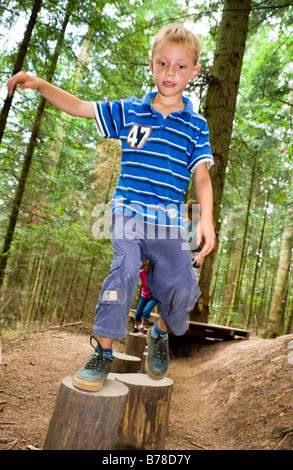 6-year-old boy balancing on a path of tree trunks - Stock Photo