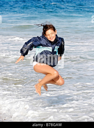 Girl, 8 years, jumping and running in the waves on the beach of Fuerteventura, Canary Island, Spain, Europe - Stock Photo
