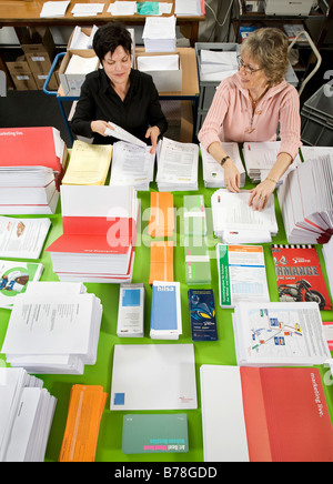 Two female employees of the logistics department of Messe Schweiz sorting and arranging brochures and papers for dispatch