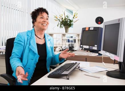 Receptionist of the Messe Schweiz AG talking to a caller over a headset, Zurich, Switzerland, Europe
