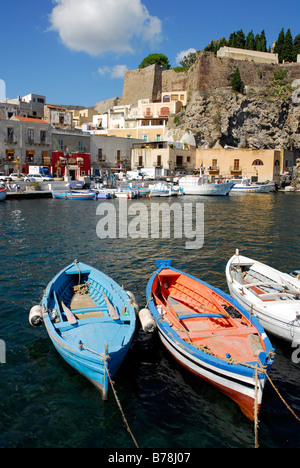Small fishing boats in the port of Marina Corta in front of the castle hill in the city of Lipari on Lipari Island, - Stock Photo