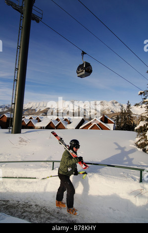 Skier in Mountain Village beneath the gondola lift, ski region Telluride in Colorado, USA, North America - Stock Photo