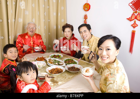 Family members in traditional clothes having dinner together and smiling at the camera - Stock Photo