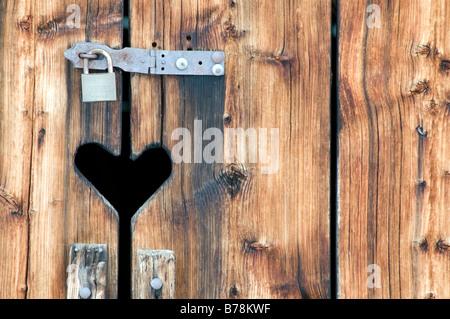 Switzerland, Arosa, Heart symbol on wooden door with padlock - Stock Photo