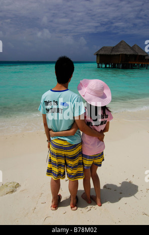 Japanese honeymooners on the beach wearing Romeo and Juliet T-shirts in Baros Resort, The Maldives, Indian Ocean - Stock Photo