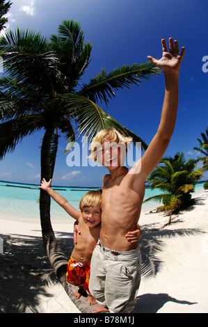 Children on a palm tree trunk in Kurumba Resort, The Maldives, Indian Ocea - Stock Photo