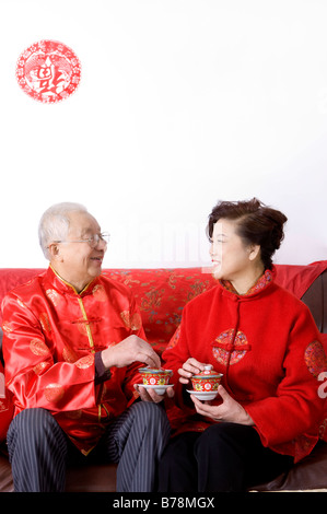 Elderly couple in traditional clothes holding tea cup and smiling at each other - Stock Photo
