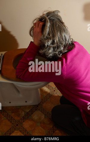 Woman pretending to be sick down the lavatory toilet - Stock Photo