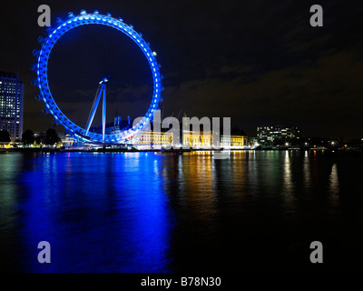 London Eye at night showing Westminster Bridge with reflections in the River Thames - Stock Photo