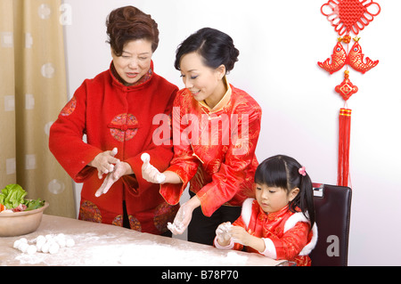 Two women and a little girl making stuffed dumplings together - Stock Photo