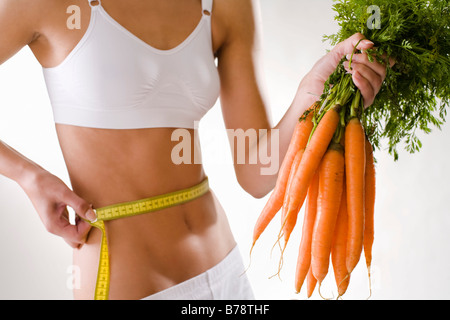 Young woman holding bunch of carrots - Stock Photo