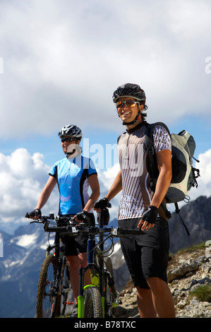 Germany, Bavaria, Karwendel, Couple with mountain bikes, taking a break - Stock Photo