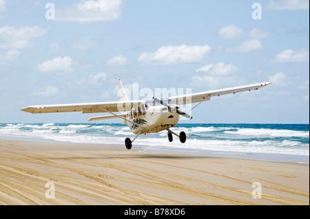 Plane landing on 75-Mile Beach, Fraser Island, Queensland, Australia - Stock Photo
