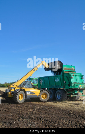 A CAT telescopic  handler  (TH330B) filled with a compost spreader. - Stock Photo
