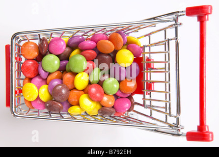 Multi-coloured candies in shopping cart, elevated view - Stock Photo