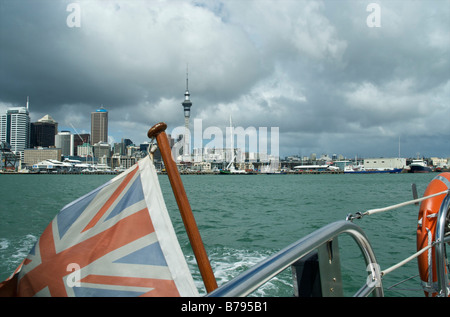 View of Auckland city panorama with Sky Tower from a saliing boat in Waitemata Harbour with dramatic clouded sky - Stock Photo