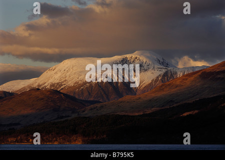 The warmly lit snow covered summit of Ben Nevis Scotland s highest mountain rises above dark foothills seen from - Stock Photo
